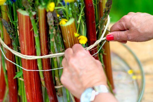 Nederland, Drachten, 04-06-2019. Bloemstyliste Esther Bolt maakt een juni bloemstuk met grassen en fruit. KM 9 Stap 6