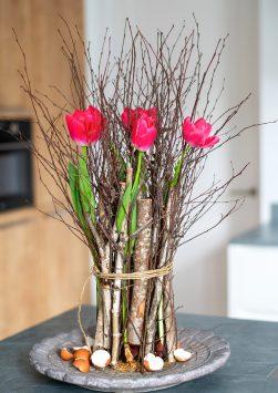 Nederland, Drachten, 23-02-2021. Bloemstyliste Esther Bolt maakt een bloemstuk van takken met daartussen in tulpen.